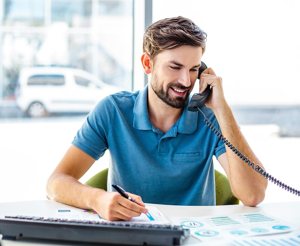 Man in blue polo shirt using StateTel business phone system
