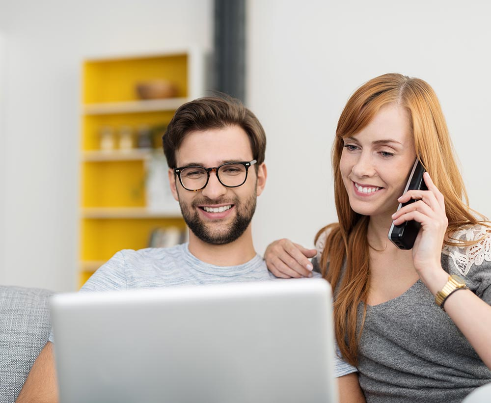 Young, attractive couple using home phone and laptop